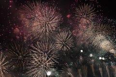 Πολλαπλάσια πυροτεχνήματα στο νυχτερινό ουρανό σε μια σύνθεση στις σκιές χρυσές και κόκκινες στοκ φωτογραφία