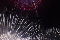 Πολλαπλάσια πυροτεχνήματα στο νυχτερινό ουρανό σε μια σύνθεση στις σκιές άσπρες και κόκκινες στοκ φωτογραφία με δικαίωμα ελεύθερης χρήσης