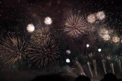 Πολλαπλάσια πυροτεχνήματα στο νυχτερινό ουρανό σε μια σύνθεση στο χρυσό σκιών στοκ εικόνες