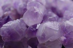Πολλαπλάσιες ορυκτές αμεθύστινες πέτρες σε μια άσπρη κινηματογράφηση σε πρώτο πλάνο υποβάθρου στοκ εικόνες