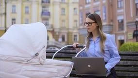 Πολλαπλών καθηκόντων μεταφορά μωρών μητέρων ταλαντεμένος και συνεδρίαση lap-top εργασίας στον πάγκο φιλμ μικρού μήκους