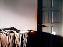 Πολλοί ένωση ενδυμασίας στην ξύλινη γραμμή ενδυμάτων κοντά στην μπλε εκλεκτής ποιότητας πόρτα με το φως του ήλιου στο διάστημα πλ Στοκ φωτογραφία με δικαίωμα ελεύθερης χρήσης