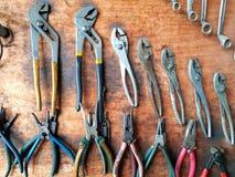 Πολλοί διαφορετικό μέγεθος του γαλλικού κλειδιού και πιό plier στο ξύλινο υπόβαθρο Στοκ Εικόνα