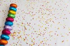 Πολλοί ευθυγράμμισαν τα χρωματισμένα αυγά Πάσχας σοκολάτας στο άσπρο υπόβαθρο και το ζωηρόχρωμο κομφετί στοκ εικόνες
