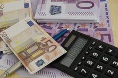 Πολλοί 500 και 50 ευρο- λογαριασμοί με μια μάνδρα και ένας υπολογιστής με ένα mi Στοκ Εικόνες