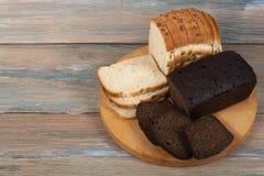 Πολλοί μικτοί ψωμιά και ρόλοι του ψημένου ψωμιού στο ξύλινο επιτραπέζιο υπόβαθρο Στοκ Εικόνες