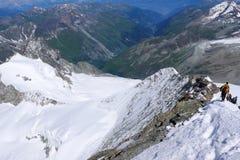 Πολλοί ορειβάτες κατεβαίνουν μια στενή και εκτεθειμένη κορυφογραμμή χιονιού στα βουνά κοντά σε Zermatt Στοκ φωτογραφία με δικαίωμα ελεύθερης χρήσης