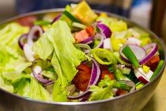 Πολλοί τεμάχισαν το φυτικό αγγουριών μαρουλιού κύπελλο σιδήρου σαλάτας αγγουριών κόκκινο, fres μεσημεριανό γεύμα Στοκ Εικόνα