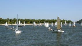 Πολλοί όμορφο να επιπλεύσει μέσο μέγεθος γιοτ πανιών με το πλήρωμα, στον ποταμό Dnieper φιλμ μικρού μήκους