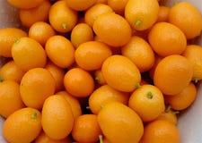 Πολλοί ώριμα πορτοκαλιά φρούτα του fortunella εσπεριδοειδών σε έναν σωρό σε ένα πιάτο ή έναν δίσκο στοκ εικόνες