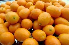 Πολλοί ώριμα πορτοκαλιά φρούτα του fortunella εσπεριδοειδών σε έναν σωρό σε ένα πιάτο ή έναν δίσκο στοκ εικόνες με δικαίωμα ελεύθερης χρήσης