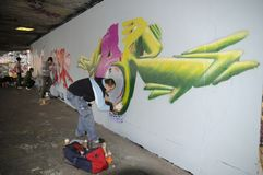 Πολυάσχολα γκράφιτι ζωγραφικής καλλιτεχνών οδών σε έναν γυμνό τοίχο Στοκ φωτογραφία με δικαίωμα ελεύθερης χρήσης