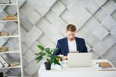 Πολυάσχολη αρσενική συνεδρίαση στον υπολογιστή γραφείου με την ταμπλέτα Στοκ Εικόνες