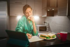 Πολυάσχολη γυναίκα που τρώει, καφές κατανάλωσης, που μιλά στο τηλέφωνο, που λειτουργεί σε ένα lap-top συγχρόνως Να κάνει επιχειρη Στοκ Φωτογραφίες