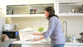 Πολυάσχολη μητέρα στην κουζίνα που φροντίζει ένα μωρό που κάνει την εργασία κουζινών απόθεμα βίντεο
