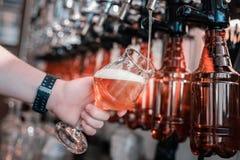 Πολυάσχολη μπύρα τεχνών μπάρμαν χύνοντας στα γυαλιά τη νύχτα της Κυριακής στοκ φωτογραφίες