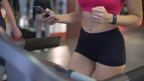 Πολυάσχολη νέα γυναίκα που χρησιμοποιεί τη συσκευή κατά τη διάρκεια του workout στη γυμναστική, που ασκεί treadmill απόθεμα βίντεο