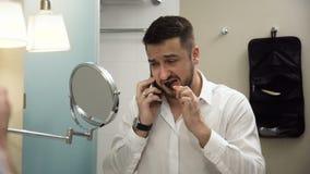 Πολυάσχολος επιχειρηματίας που μιλά στο τηλέφωνο βουρτσίζοντας τα δόντια φιλμ μικρού μήκους