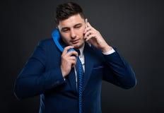 Πολυάσχολος επιχειρηματίας στην εργασία που μιλά σε δύο τηλέφωνα Στοκ εικόνα με δικαίωμα ελεύθερης χρήσης