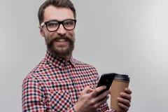Πολυάσχολος εργατικός επιχειρηματίας που φορά τα γυαλιά που κρατούν το take-$l*away καφέ στοκ φωτογραφία