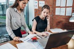 Πολυάσχολος θηλυκός τοπ διευθυντής που μιλά στο τηλέφωνο ενώ ο βοηθός της που παρουσιάζει οικονομικές στατιστικές της Στοκ φωτογραφία με δικαίωμα ελεύθερης χρήσης