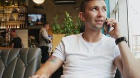 Πολυάσχολος νεαρός άνδρας που μιλά σε ένα τηλέφωνο κυττάρων σε έναν καφέ φιλμ μικρού μήκους