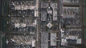 Πολυάσχολος σύγχρονος αερολιμένας με τα αεροπλάνα και αεροσκάφη κατά τη τοπ εναέρια άποψη πανοράματος κηφήνων βιομηχανική φιλμ μικρού μήκους