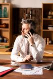 Πολυάσχολο άτομο που μιλά τηλεφωνικώς στην κουζίνα στοκ φωτογραφίες