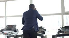 Πολυάσχολο αρσενικό αφροαμερικάνων στο κοστούμι που τρέχει treadmill και που μιλά στο τηλέφωνο απόθεμα βίντεο