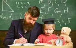 Πολυάσχολο παιδί που μελετά στο σχολείο Δάσκαλος, πατέρας που ελέγχει την εργασία, βοήθειες στο αγόρι, γιος Δάσκαλος στην επίσημη Στοκ Εικόνες