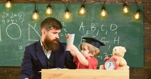 Πολυάσχολο παιδί που μελετά στο σχολείο Δάσκαλος, πατέρας που ελέγχει την εργασία, βοήθειες στο αγόρι, γιος Μεμονωμένη έννοια μελ Στοκ Φωτογραφία