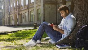 Πολυεθνική νέα αρσενική συνεδρίαση κάτω από το δέντρο, πιάνοντας βιβλίο ανάγνωσης, έκπληκτο Στοκ εικόνες με δικαίωμα ελεύθερης χρήσης