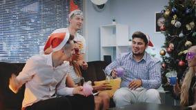 Πολυεθνική νεολαία στα καπέλα Santa και τις μάσκες κομμάτων που κάνουν τις ευθυμίες στα Χριστούγεννα απόθεμα βίντεο