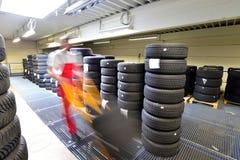 Πολυκατάστημα με τα ελαστικά αυτοκινήτου αυτοκινήτων σε ένα γκαράζ - αλλαγή ελαστικών αυτοκινήτου Στοκ Εικόνα