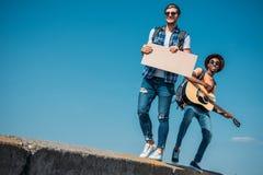 πολυπολιτισμικά άτομα με το κενό χαρτόνι που περπατούν στο στηθαίο ενώ Στοκ Εικόνες