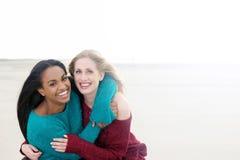 Πολυπολιτισμικά κορίτσια που χαμογελούν και που αγκαλιάζουν Στοκ Εικόνες