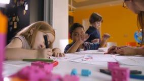 Πολυπολιτισμικά παιδιά που απολαμβάνουν το σχέδιο στο μάθημα τέχνης απόθεμα βίντεο