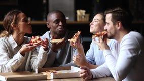 Πολυπολιτισμική ευτυχής ομιλία φίλων που γελά μοιραμένος το take-$l*away γεύμα πιτσών από κοινού φιλμ μικρού μήκους