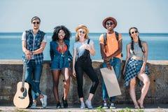 πολυπολιτισμική ομάδα νέων με το κενό χαρτόνι που στέκεται ένα στηθαίο ενώ Στοκ Φωτογραφία