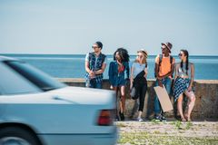 πολυπολιτισμική ομάδα νέων με το κενό χαρτόνι που στέκεται ένα στηθαίο ενώ Στοκ εικόνες με δικαίωμα ελεύθερης χρήσης