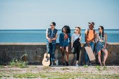 πολυπολιτισμική ομάδα νέων με το κενό χαρτόνι που στέκεται ένα στηθαίο ενώ Στοκ εικόνα με δικαίωμα ελεύθερης χρήσης