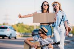 πολυπολιτισμικοί φίλοι με το κενό χαρτόνι που κάνουν ωτοστόπ ενώ Στοκ Φωτογραφία