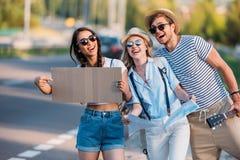 πολυπολιτισμικοί φίλοι με το κενό χαρτόνι που κάνουν ωτοστόπ ενώ Στοκ Εικόνα