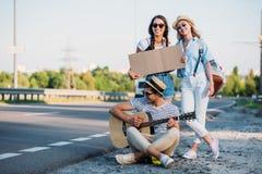 πολυπολιτισμικοί φίλοι με το κενό χαρτόνι που κάνουν ωτοστόπ ενώ Στοκ εικόνα με δικαίωμα ελεύθερης χρήσης