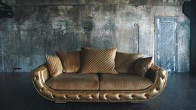 Πολυτελής καναπές σε ένα σύγχρονο interio Στους σκοτεινούς τόνους και τις σκιές του χρυσού απόθεμα βίντεο