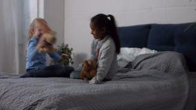 Πολυφυλετικά παιδιά που παίζουν τα παιχνίδια βελούδου στο σπίτι απόθεμα βίντεο