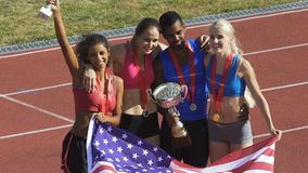 Πολυφυλετική αθλητική ομάδα από τις ΗΠΑ που παρουσιάζουν τα φλυτζάνια και τρόπαια, νίκη ανταγωνισμού απόθεμα βίντεο