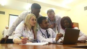 Πολυφυλετική ομάδα των νέων γιατρών που εργάζονται στο φορητό προσωπικό υπολογιστή στο ιατρικό γραφείο απόθεμα βίντεο