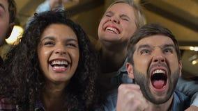Πολυφυλετικοί ανεμιστήρες που υποστηρίζουν την αγαπημένη αθλητική ομάδα στο μπαρ, ενθαρρυντικό για τη νίκη απόθεμα βίντεο