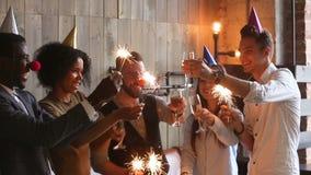 Πολυφυλετικοί νέοι που κρατούν τα sparklers που τα γυαλιά που γιορτάζουν το κόμμα, ευθυμίες απόθεμα βίντεο